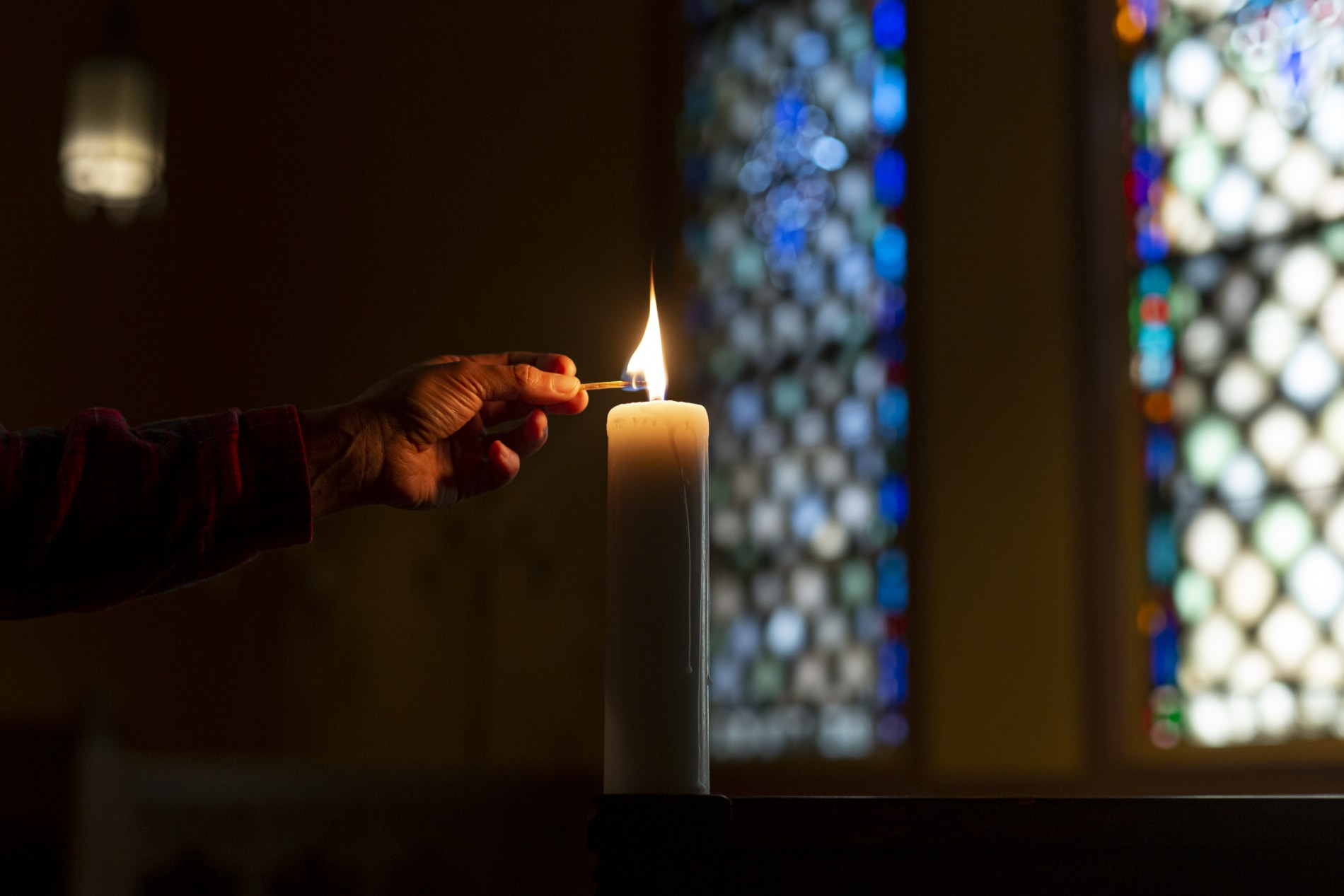 someone lighting a candle