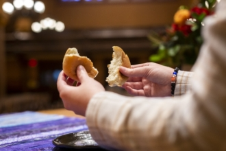 A woman breaks bread during communion