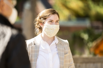 A woman wearing a mask gathers with a group of people at church