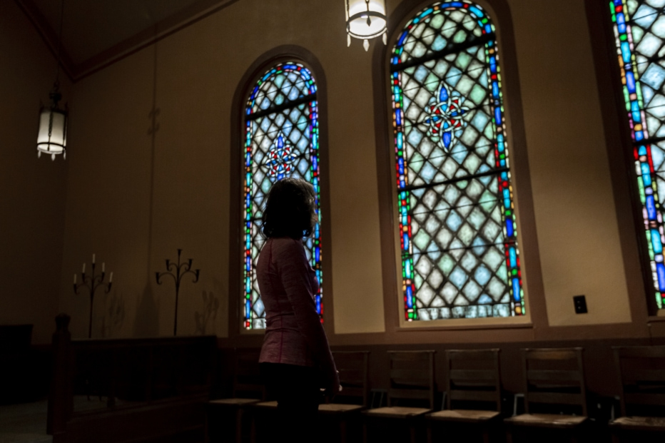 A woman looks at stained glass windows in a church