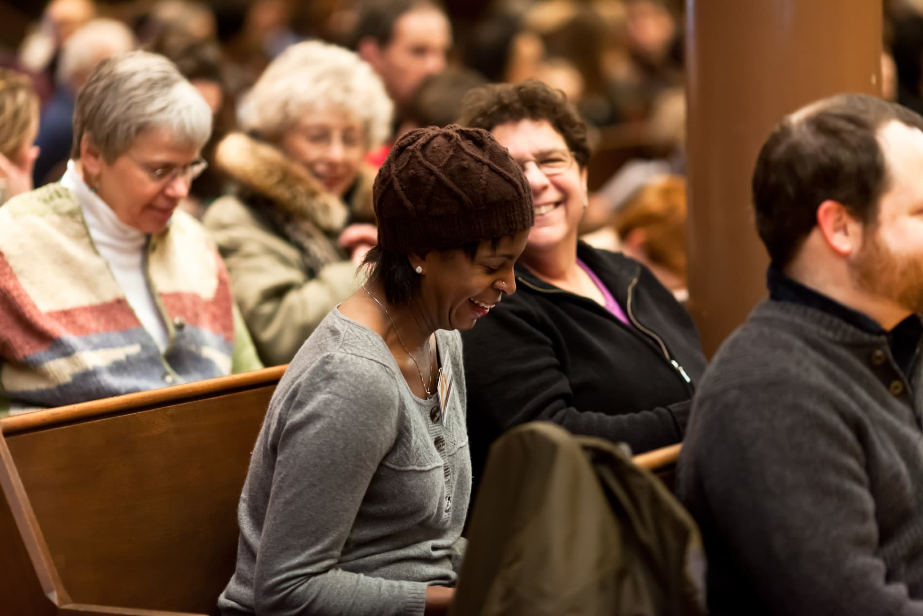 Two women sit in a pew and laugh