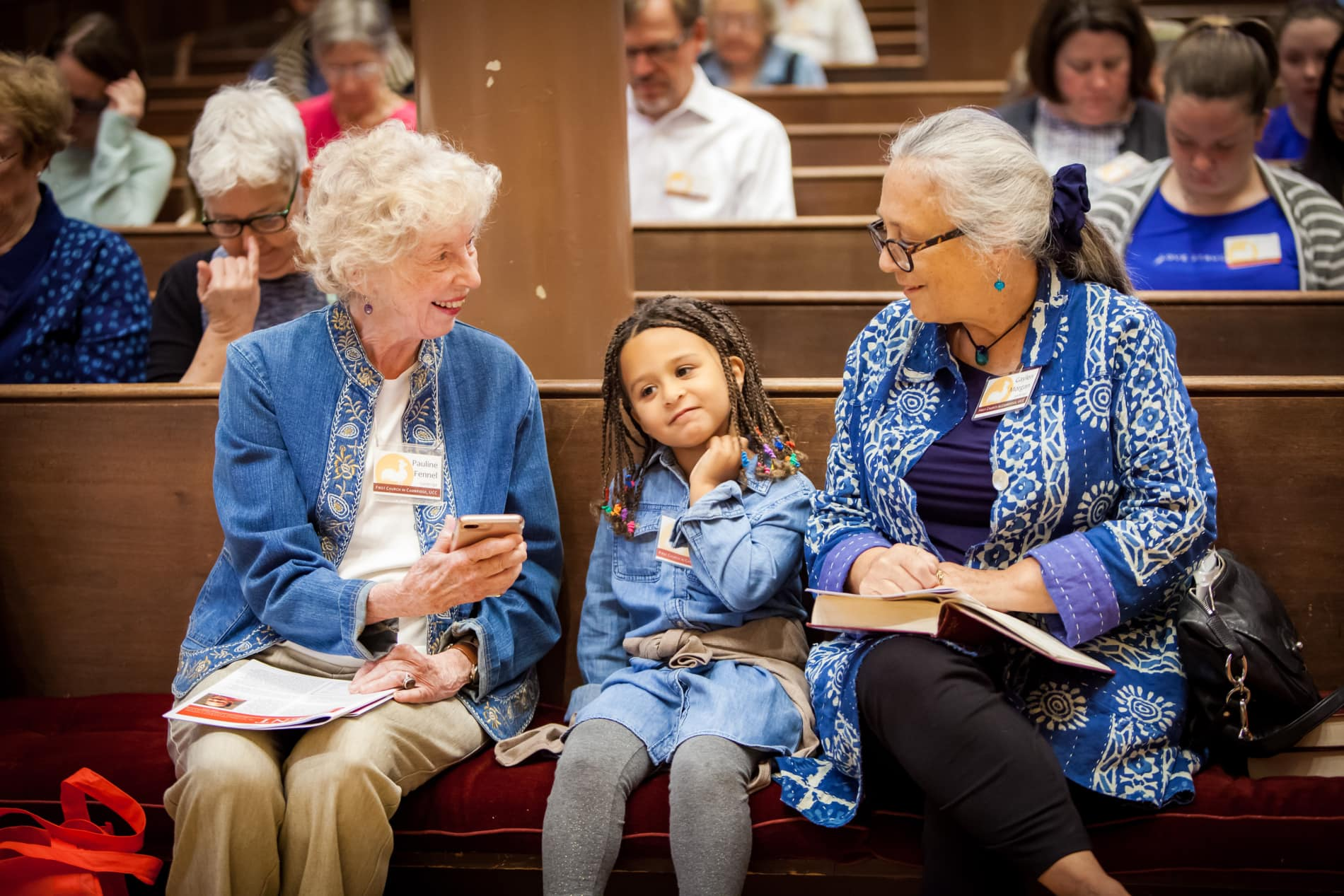 two older women with a little girl in church