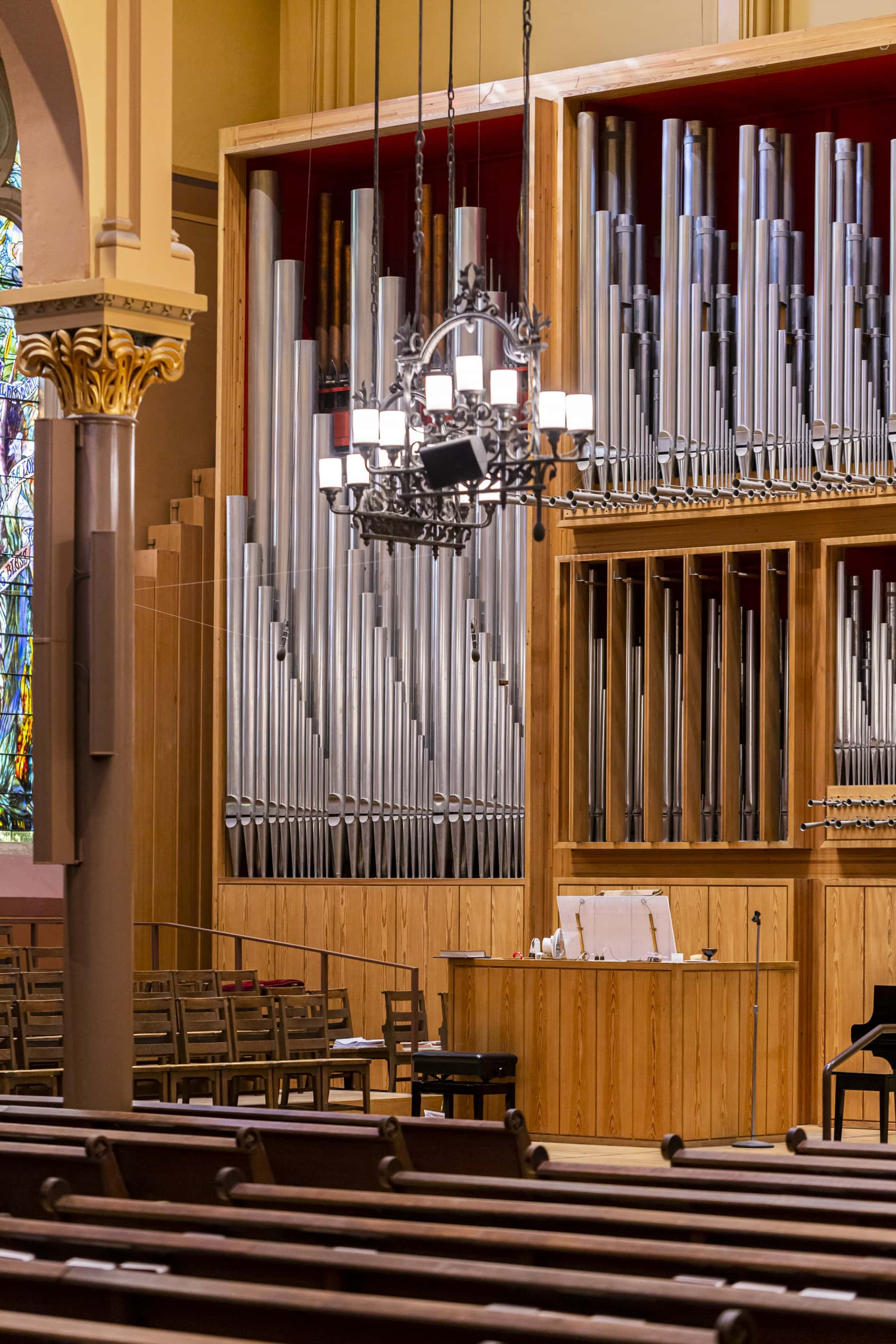 Organ pipes in the Sanctuary of First Church in Cambridge. A wrought iron chandelier hangs in the foreground.