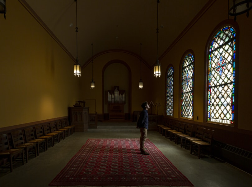 person standing in a chapel alone in darkness