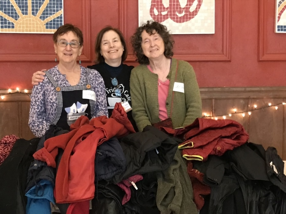 three women standing behind clothing donations