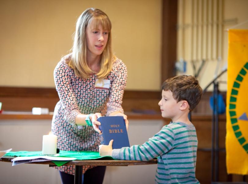 Church School teacher and student begin their class with worship.
