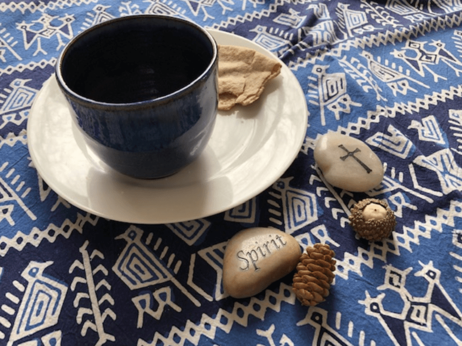 a cup and plate on a table cloth