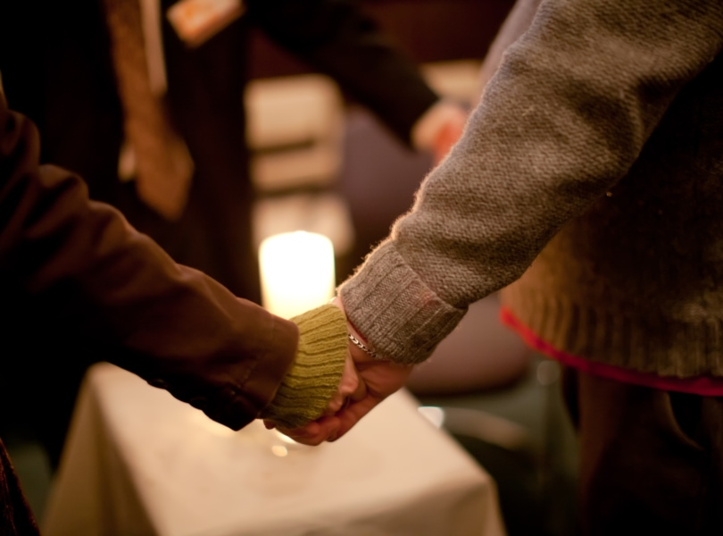 people holding hands around a candle